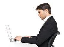 Büroangestellter mit dem Laptop, der auf der Tabelle sitzt Stockfotografie