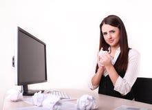 Büroangestellter mit geschraubtem oben Papierball auf ihrem nicht schauenden Schreibtisch Lizenzfreie Stockfotos