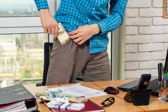 Büroangestellter setzt ein Pack des Geldes in seine Tasche ein stockbild