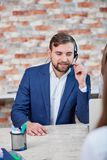 Büroangestelltmann mit Kopfhörern sitzt am Schreibtisch und bearbeitet das Sprechen in das Mikrofon der Kopfhörer Lizenzfreies Stockfoto