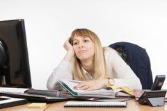 Büroarbeit ermüdete einen Spezialisten, um Ordner mit Dokumenten heraus zu sortieren und betrachtete traurig dem Bildschirm Lizenzfreie Stockfotos