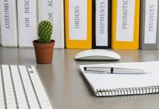Büroarbeitsplatz auf grauem Schreibtisch mit Kaktus und Stockbild