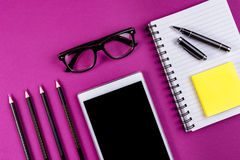 Büroartikel auf purpurrotem Hintergrund Lizenzfreie Stockfotografie
