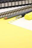 Büroartikel, Bleistifte, Markierungsnotizbücher, die auf gelbem Schreibtisch liegen Stockbilder