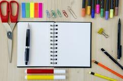 Büroartikel, der auf einen hölzernen Schreibtischhintergrund legt Beschneidungspfad eingeschlossen Bleistifte, Scheren, Markierun Lizenzfreie Stockfotografie