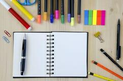 Büroartikel, der auf einen hölzernen Schreibtischhintergrund legt Beschneidungspfad eingeschlossen Bleistifte, Scheren, Markierun Stockfotografie