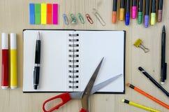 Büroartikel, der auf einen hölzernen Schreibtischhintergrund legt Beschneidungspfad eingeschlossen Bleistifte, Scheren, Markierun Stockfotos