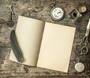 Büroartikel des offenen Buches und der Weinlese versieht Stift, Tintenfaß mit Federn Lizenzfreie Stockfotos