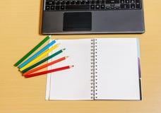 Bürodesktop mit Laptop, geöffnetem Notizbuch und Bleistiften Lizenzfreies Stockfoto