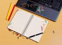 Bürodesktop mit Laptop, geöffnetem Notizbuch und Bleistiften Stockbilder