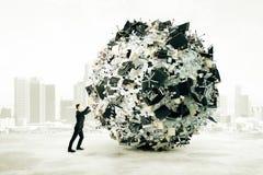 Bürodumpkonzept mit dem Geschäftsmann, der einen großen Ball von offic drückt Stockfotografie