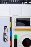 Büroeinzelteile, Gläser, Laptop, Telefon und ein Tasse Kaffee auf Whit Stockbild
