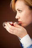 Bürofrau, die mit heißem Tee sich entspannt lizenzfreie stockbilder