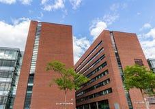 Bürogebäude gegen blauen Himmel mit Wolken und Sonne beleuchten Stockbilder