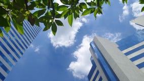 Bürogebäude und Baum unter weißen Wolken und blauem Himmel auf dem wärmsten Mittag in Thailand Lizenzfreies Stockfoto