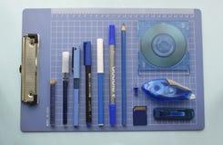 Bürogegenstände vereinbart im blauen Gitter stockbild
