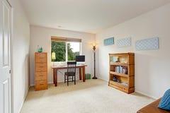 Büroinnenraum mit einfachem Schreibtisch und Bücherregal Stockfotos