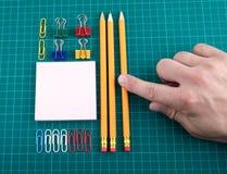 Büroklammern, Bleistifte und Anmerkung bedecken auf überprüftem grünem backgound Stockfotografie