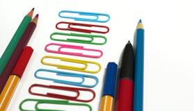 Büroklammern, farbige Bleistifte und Stifte in der Folge gesetzt Stockbild