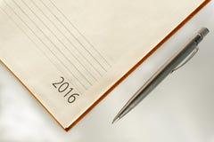 Büroorganisatorkalender 2016 und -splitter des neuen Jahres ballpen Stockbild