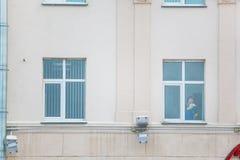 Büroreiniger, der das Fenster innerhalb des modernen Gebäudes poliert stockbild