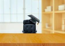 Bürostuhl mit Hochschulstaffelungshut Stockbild