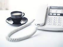 Bürotelefon und -cup stockbild