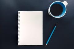 Bürotisch mit leerem Notizblock, Bleistift und Tasse Kaffee Stockfoto