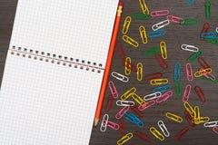 Bürotisch mit Notizbuch, Bleistiften und Büroklammern Stockfoto