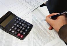 Bürotisch mit Taschenrechner, Stift und Buchhaltungsdokument Stockbild