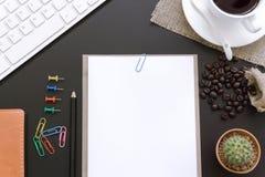 Bürotischplattenansicht, Blume, Kaffeetasse und Buch Lizenzfreie Stockbilder