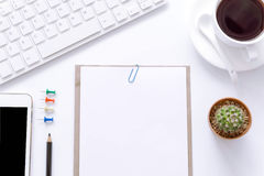 Bürotischplattenansicht mit Smartphones, Blume, Kaffeetasse und Buch Lizenzfreie Stockfotografie
