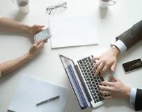 Bürotischplattenansicht, weiblich am Telefon, Mann auf Laptop stockbilder