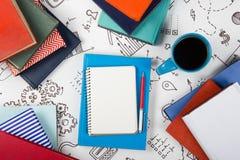 Bürotischschreibtisch mit Blauversorgungen, weißer leerer Notizblock, Schale, Stift, PC, zerknitterte Papier, Blume auf hölzernem Stockbild