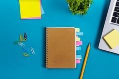 Bürotischschreibtisch mit Satz bunten Versorgungen, weißer leerer Notizblock, Schale, Stift, PC, zerknitterte Papier, Blume auf B Lizenzfreie Stockfotos