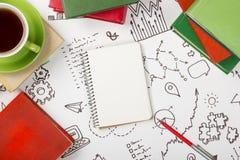 Bürotischschreibtisch mit Versorgungen, leerer Notizblock, Schale, Stift auf weißem Hintergrund der Geschäftsstrategie Draufsicht Lizenzfreie Stockfotografie