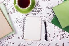 Bürotischschreibtisch mit Versorgungen, leerer Notizblock, Schale, Stift auf weißem Hintergrund der Geschäftsstrategie Draufsicht Lizenzfreie Stockfotos