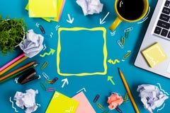 Bürotischschreibtisch mit Versorgungen, weißer leerer Notizblock, Schale, Stift, PC, zerknitterte Papier, Blume auf blauem Hinter Stockbild