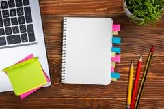Bürotischschreibtisch mit Versorgungen, weißer leerer Notizblock, Schale, Stift, PC, zerknitterte Papier, Blume auf hölzernem Hin Lizenzfreie Stockbilder
