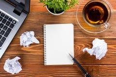 Bürotischschreibtisch mit Versorgungen, weißer leerer Notizblock, Schale, Stift, PC, zerknitterte Papier, Blume auf hölzernem Hin Lizenzfreies Stockbild