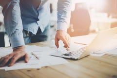 Bürowelt Geschäftsmann, der am hölzernen Tisch mit neuem Geschäftsprojekt im modernen coworking Platz arbeitet Mannberühren