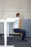 Büroyoga - Geschäftsmann, der am Stehpult trainiert Stockbilder