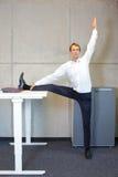 Büroyoga - Geschäftsmann, der am Stehpult trainiert Stockfoto