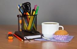Bürozubehör, Tasse Kaffee und Kuchen Lizenzfreie Stockfotografie
