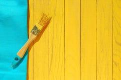 Bürste in der gelben Farbe auf blauem und gelbem hölzernem Hintergrund Stockbild