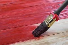 Bürste malt ein hölzernes Brett zum Rot Lizenzfreie Stockfotos