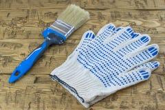 Bürste mit Handschuhen auf einem Holztisch Stockbild