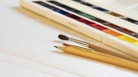 Bürste und Bleistift auf dem Hintergrund des Aquarells malt Seitenansicht der Nahaufnahme lizenzfreie stockfotografie