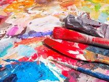 Bürste und helle Ölfarbenpalette für Hintergrund Stockfotos