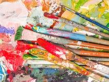 Bürste und helle Ölfarbenpalette für Hintergrund Lizenzfreie Stockfotos